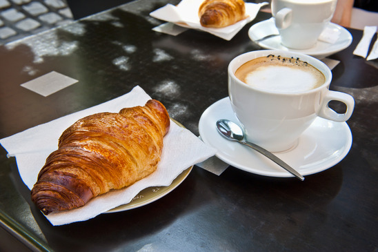 a breakfast of Croissant & Cappuccino at a sidewalk restaurant in France